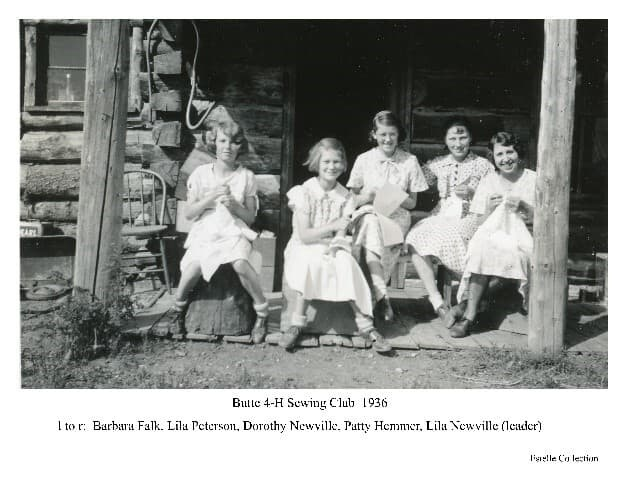 Image shows four girls and one women in white dresses sitting on the porch of a log cabin, each appears to be stitching a piece of cloth. The group is collectively identified as the Butte 4-H Sewing Club and individually identified from left as: Barbara Falk, Lila Peterson, Dorothy Newville, Patty Hemmer, and the woman is identified as Lila Newville, the club leader.