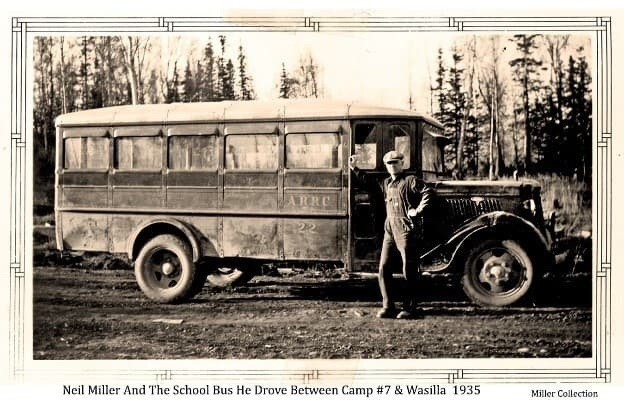 Image shows a man, identified as Neil Miller, standing in front of a bus, identified as ARRC bus #22 used to transport school children from Colony camp #7 to the Wasilla school. The bus is on a gravel road with trees behind.