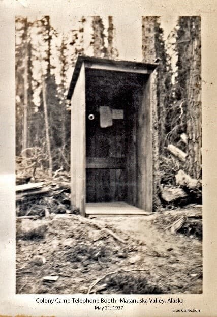 """Image shows an open wooden """"phone booth"""" with telephone and papers evident on the back back wall. Located in a rough wooded setting. Location described above is assumed from associated photos in the collection."""