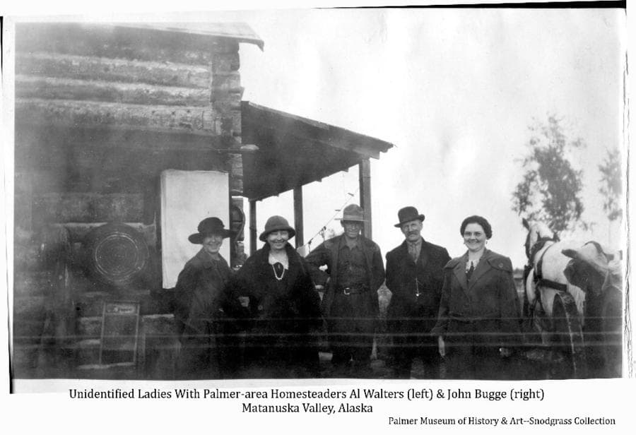 Image shows homesteaders Al Walters (left) & John Bugge standing with three unidentified women next to a log building. A white horse harnessed to a cart is at right, a wash tub and washboard are evident on the cabin wall.