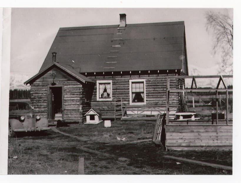 Image shows an early spring view of a log house with entry porch, a car parked next to the porch, a small doghouse next to the porch, an uncovered greenhouse in foreground, forest and snow-clad mountains beyond. This appears to be the south side of House#4.