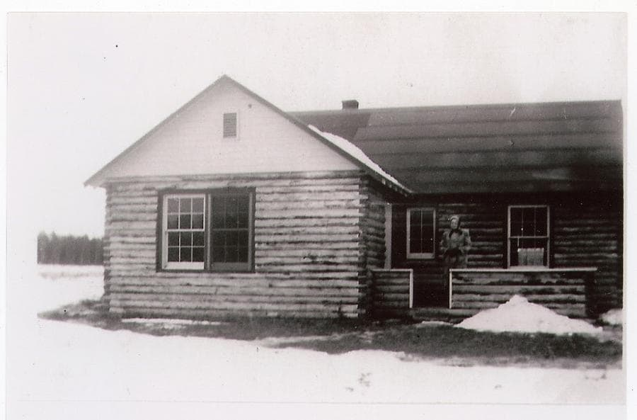 Image is a winter view of a log house with a woman standing in the entry porch area, forest is visible beyond.