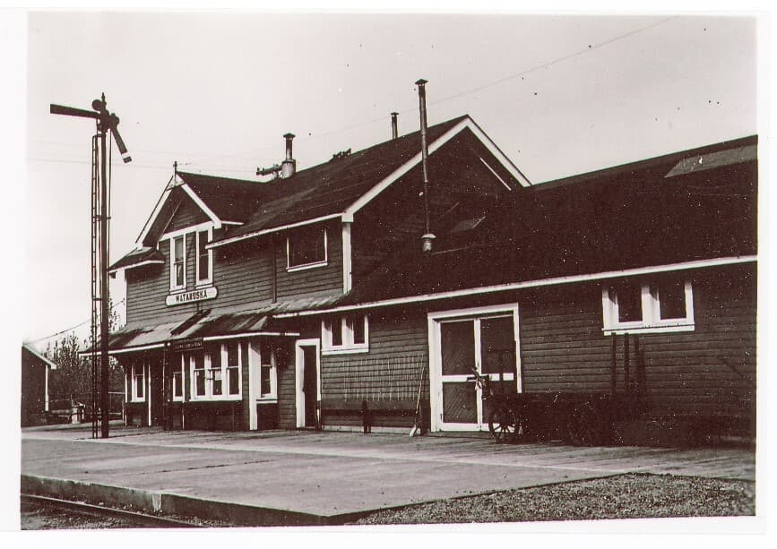 Image shows the track-side view of the Matanuska depot building looking south, with a semaphore signal pole on the left, both wood and concrete dock in foreground, a baggage cart, and a flower box with strings attached to the wall to support climbing flowers. No flowers are evident.