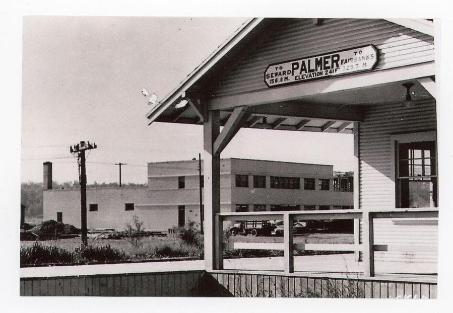 Image shows the south end of the Palmer railroad depot and Koslosky's department store across the street beyond. Automobiles parked in front of Koslosky's are partly visible. The Valley Hotel under construction next to the store is partially visible. The hotel was constructed in 1946-47 & opened in 1948. Evidence of its partial completion identifies the photo date as probably 1947.