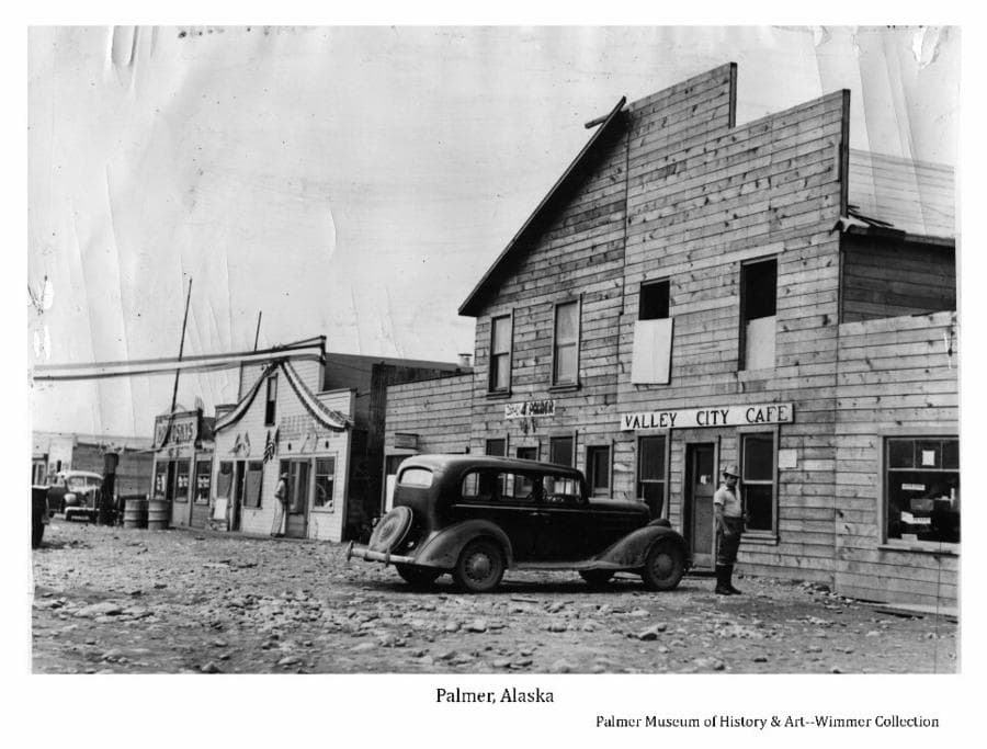 Image shows a summer view of Palmer's gravel street in foreground and numerous buildings in foreground and middle ground. Several buildings exhibit business signs. Valley City Café is prominent. A car is prominent in foreground and another car is parked in middle ground near a gas pump and barrels in front of Koslosky's store. Two men are evident. Bunting and flags decorate the front of one building with a bunting ribbon stretched above the street.
