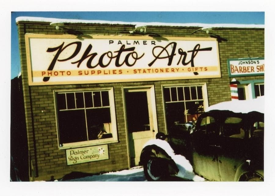 """Color image shows storefront """"Palmer Photo Art"""" & """"Johnson's Barber Shop"""" with a car parked in front, snow on ground & car."""
