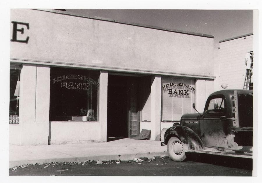 The image shows a summer view of the northern end of Koslosky's Department Store occupied by Matanuska Valley Bank with the bank signs in the windows. A truck is parked in front of the bank. A workman is visible standing on a ladder at the top story window of the Valley Hotel at right.