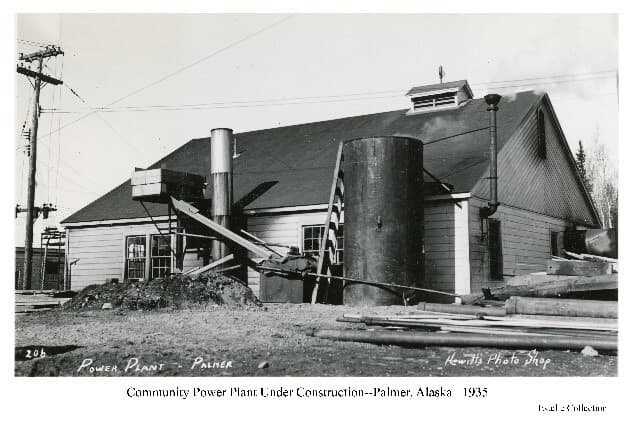 Image shows the southeast view of the community Powerhouse, exterior construction partially complete with smokestack partly installed. Construction material is visible in foreground.