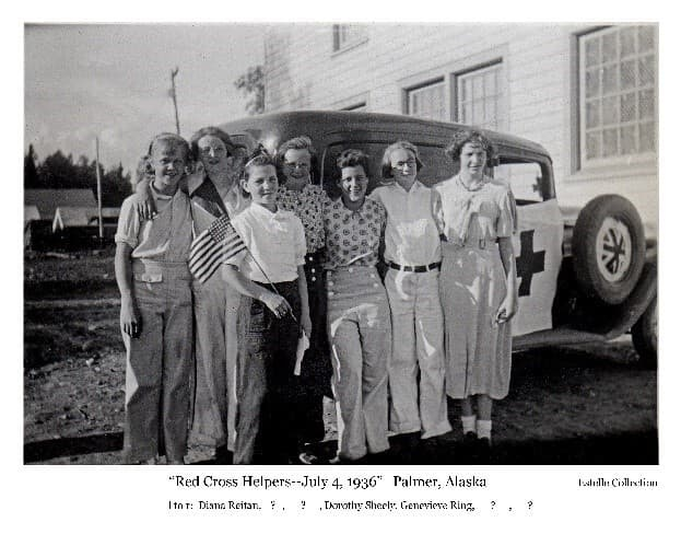 """Image shows a group of young women, all """"Colony Kids"""" identified from left to right as Diana Reitan, unknown, unknown, Dorothy Sheely, Genevieve Ring, unknown, and unknown, standing in front of a vehicle, identified as the hospital """"Nurses Car"""" and ambulance which was part of the Palmer Fourth-of-July parade. Colony Tents and the Hospital building are in the background. One girl holds a 48-star flag."""