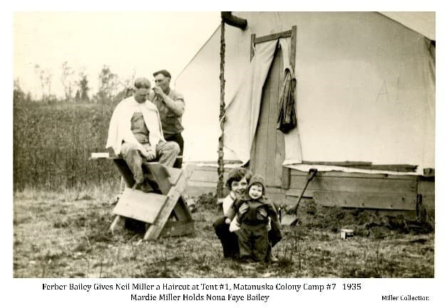 """Image Shows a man, identified as colonist Neil Miller, sitting on a sawbuck in from of a white tent and receiving a haircut from another man, identified as colonist Ferber Bailey. Two children are in the foreground, identified as Mardie Miller holding Nona Faye Bailey. The tent is a typical Colony tent with """"A-1"""" visibly marked on the canvas. The setting is identified as Colony Camp #7 northwest of Palmer."""