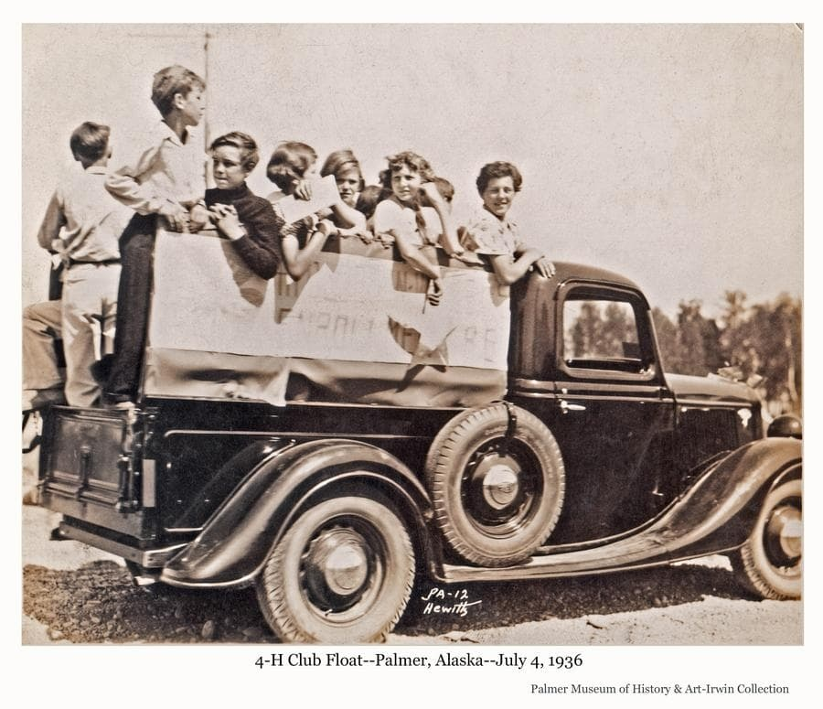 Image shows a group of children in the back of a pick-up truck.  A banner on the side of the truck indicates it is a 4-H entry in the July 4th parade.