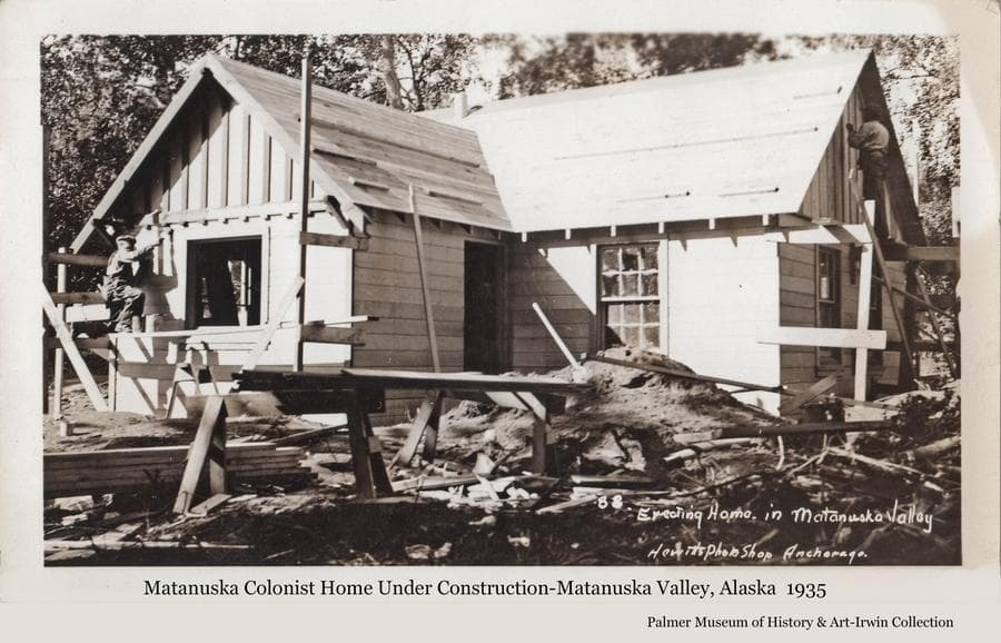 """Image shows a Colony home under construction.  Homes not built of logs were referred to by the government as """"cottages"""".  Two men are visible working on scaffolding on the outside of the house.  Considerable debris is apparent in the yard."""