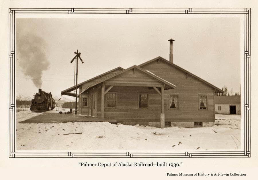 Image is a winter scene of the south end of the Palmer railroad depot.  A train engine is at the left and the Co-op garage building is partially visible at right.