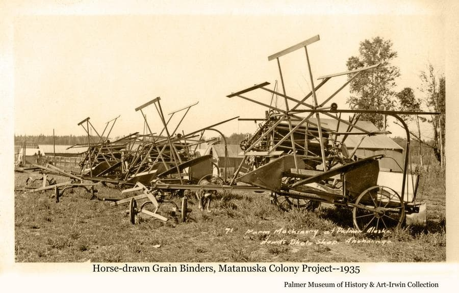"""Image shows a row of horse-drawn grain binder machines in Palmer waiting to be made available to colony farmers when they became needed for harvesting as the Colonists produced grain crops.  Tents and other buildings of the """"Tent City"""" are visible behind the binders."""