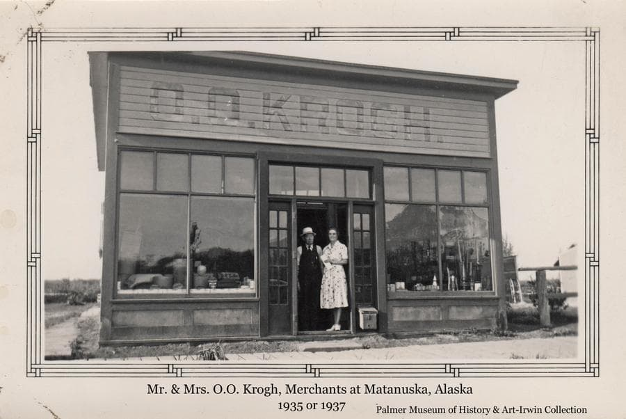 """Image is of Mr. & Mrs. O.O. Krogh, merchants of the community of Matanuska, standing in the doorway of their store.  The front of the frame store is prominent with large glass display windows capped with smaller decorative windows, and """"O.O. KROGH."""" painted above."""