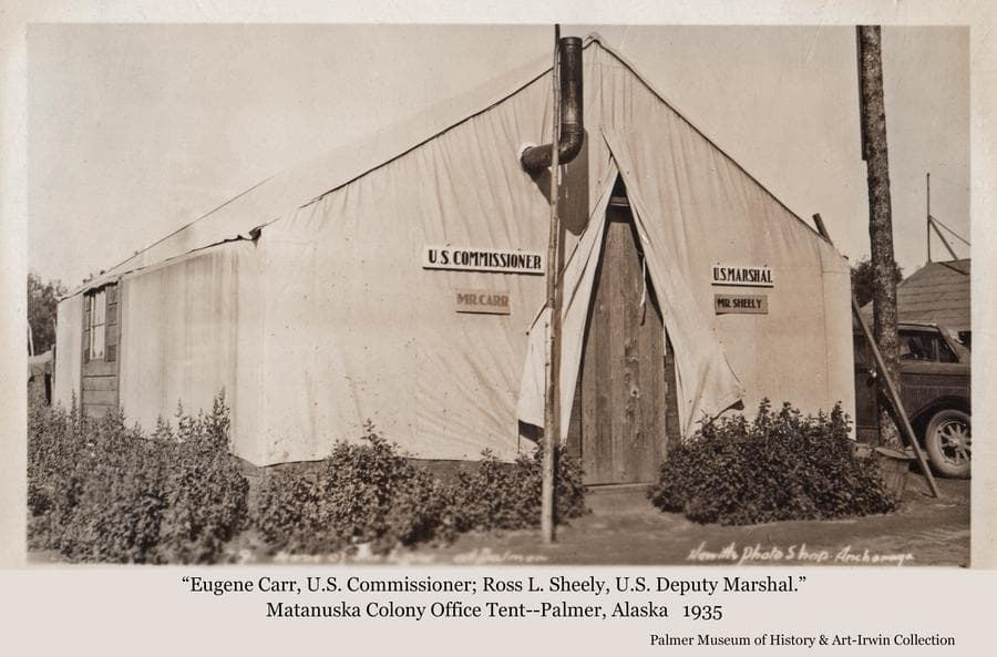 """Image is of a tent with signs on the front indicating it held offices of """"Mr. Carr, U.S. Commissioner"""" and """"Mr. Sheely, U.S. Marshal"""".  A portion of an automobile is visible beside the tent to the right."""