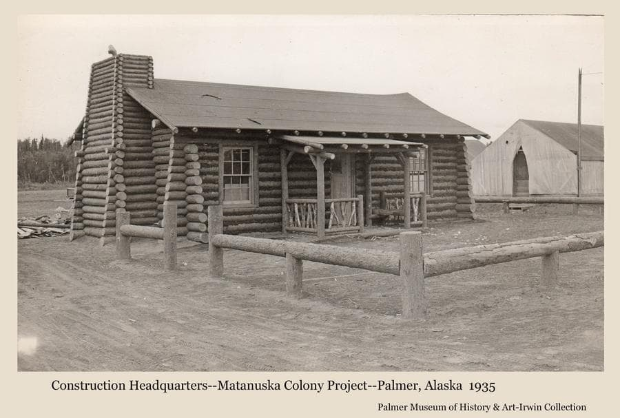 Image shows the first log building constructed by the transient workers employed to build the new buildings associated with the Matanuska Colony.  The building was thought to have been disassembled and reassembled as a training exercise for the workers, and then served as the headquarters for the rest of the construction activities.   A low log fence encloses the front yard.  A tent is partially visible at right.
