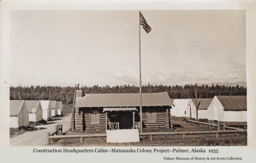 Image shows the first log building constructed by the transient workers employed to build the new buildings associated with the Matanuska Colony.  The building was thought to have been disassembled and reassembled as a training exercise for the workers, and then served as the headquarters for the rest of the construction activities.  The American flag flies on a tall pole over the building.  A low log fence encloses the yard.  Tents are apparent on both sides of the building.  Heavy forest forms a backdrop behind.