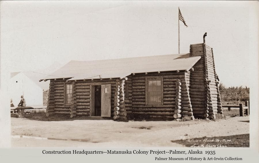 Image shows the first log building constructed by the transient workers employed to build the new buildings associated with the Matanuska Colony.  The building was thought to have been disassembled and reassembled as a training exercise for the workers, and then served as the headquarters for the rest of the construction activities.   The American flag flies above the building on a high mast.   A tent is partially visible at left and a man is standing nearby.