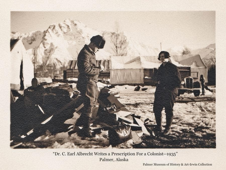 Image is a winter scene showing Dr. C. Earl Albrecht, Matanuska Valley physician, standing beside a woodpile writing a prescription for a woman nearby.  At his feet are two medical bags, one opened and exhibiting its contents while perched on the piled wood.  Tents are in middle ground and a truck is partially visible behind the woman with a man standing next to it.  Snow-clad Pioneer Peak is in background.