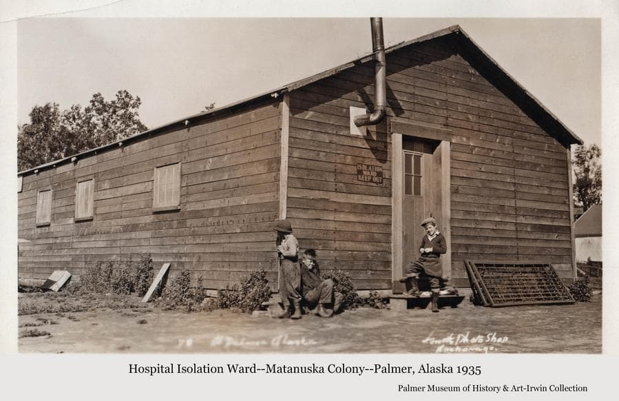 """Image is of three young boys hanging around the front of a wood frame building.  A sign on the front of the building reads: """"ISOLATION WARD  KEEP OUT"""".  Two bed spring frames lean against the front of the building and a tent is partially visible at right."""