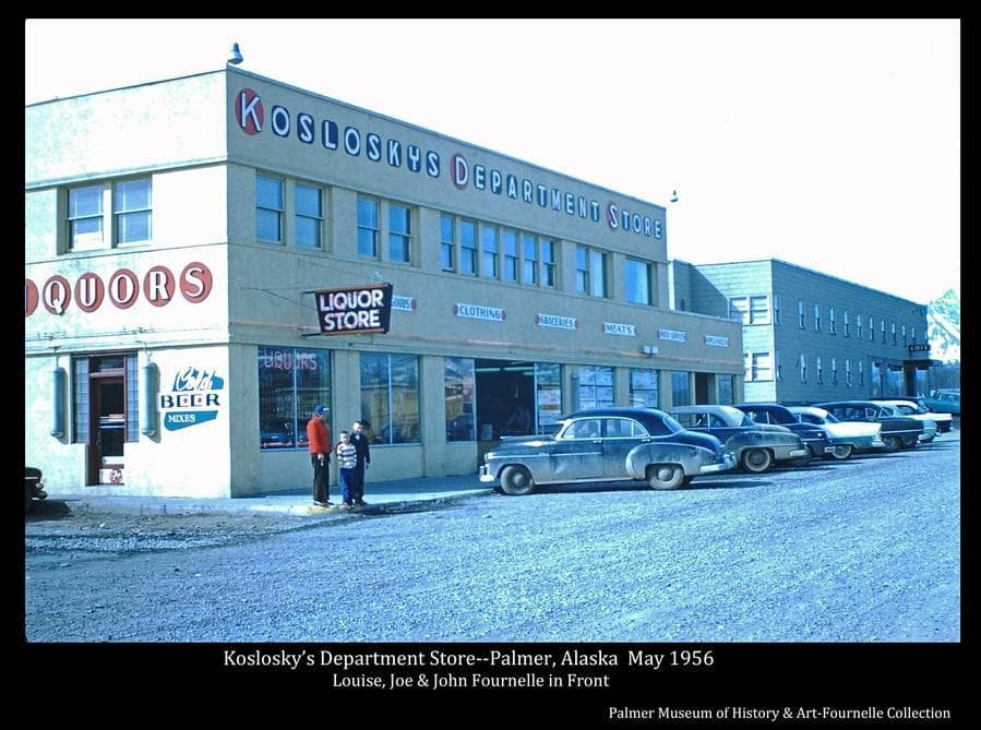 Photo is a color scene showing Koslosky's Department store and the Valley Hotel with several cars parked at the curb.  Signs are evident.  Louise, Joe Jr. and John Fournelle stand on the sidewalk.