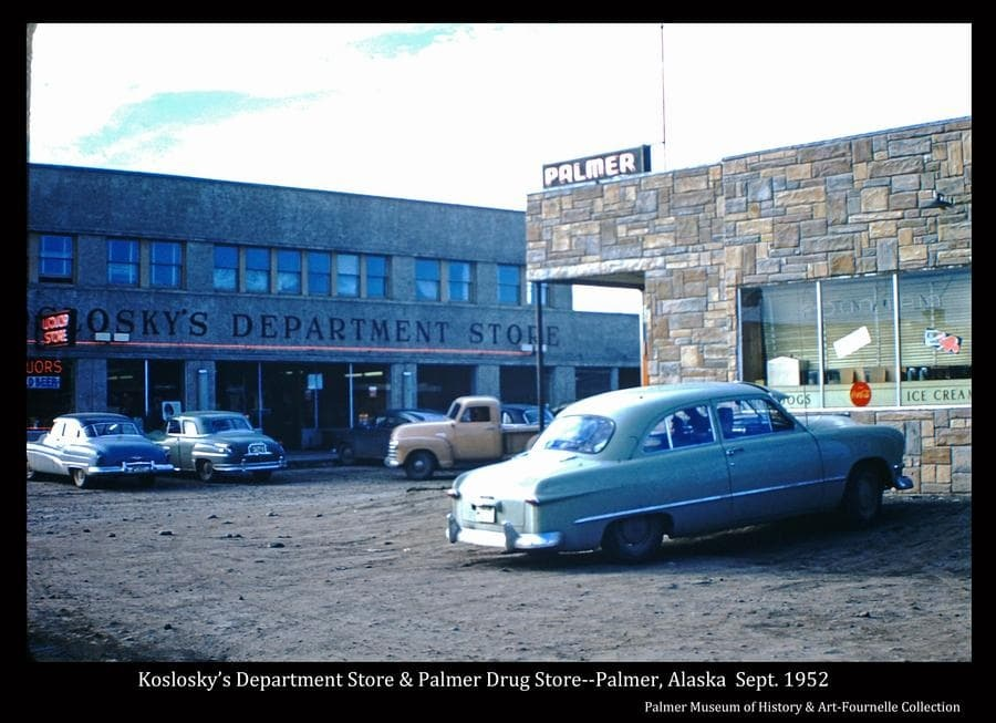 This photo is a color scene in downtown Palmer, showing a car parked next to the Palmer Drugstore in foreground, identified as the 1950 Ford belonging to the Fournelle family, with Koslosky's Department Store apparent across the street.  Cars are parked in front of Koslosky's and a pickup is on the street.  Signs are evident.