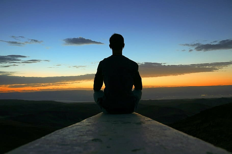 Beautiful view of a man meditating facing the sunset.