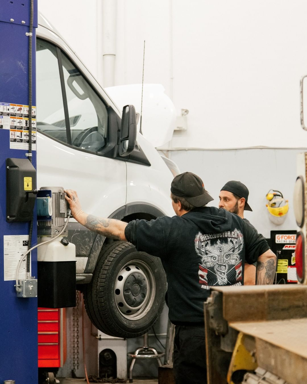 Mechanics using lift in diesel shop