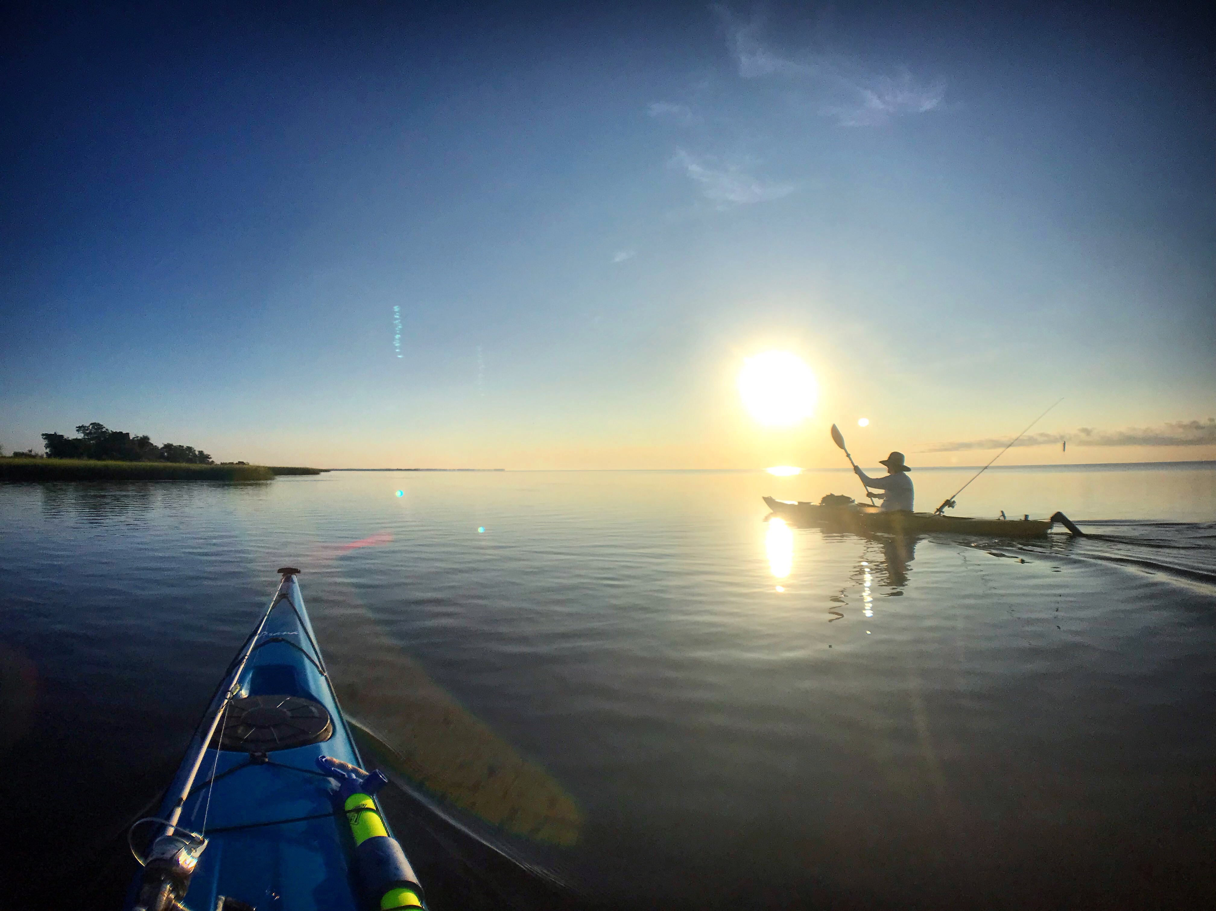 Two kayakers paddling on the open water at sunset.