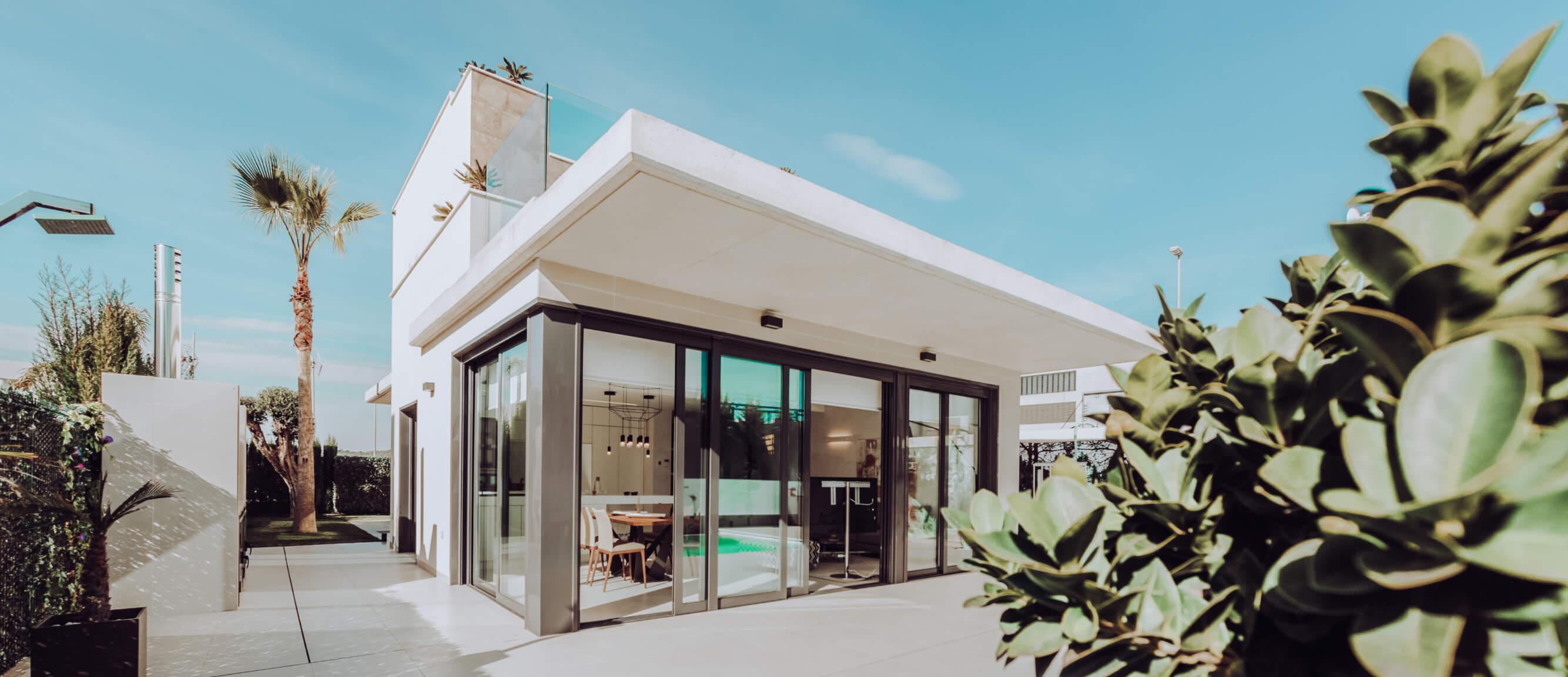 Большой белый дом с темными раздвижными окнами и бассейном.