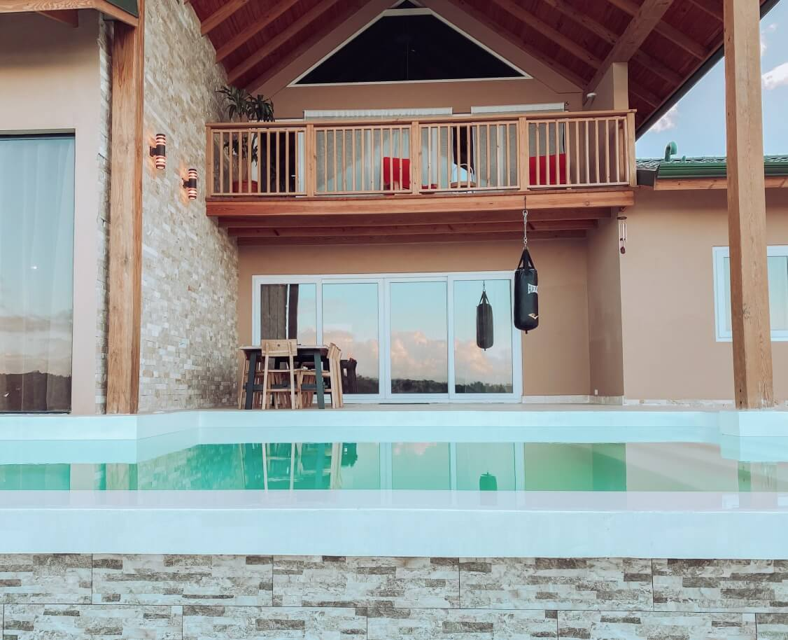 Vista frontal de una casa con piscina y puertas corredizas. Presa de Taveras, La Vega. República Dominicana.