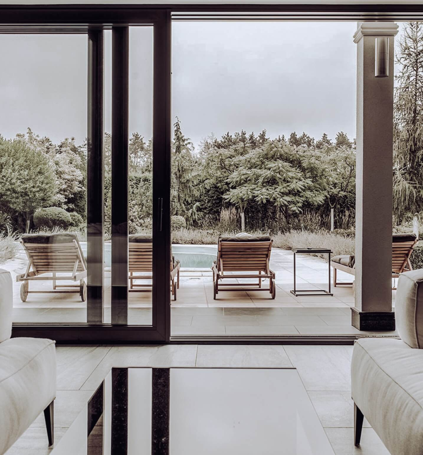 Dark sliding doors showing a view over the pool area in a house.