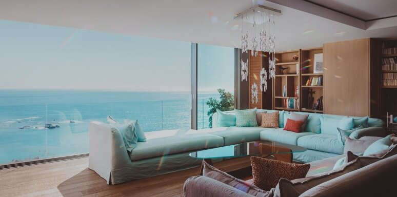 Big windows with a view over the ocean from a living room.