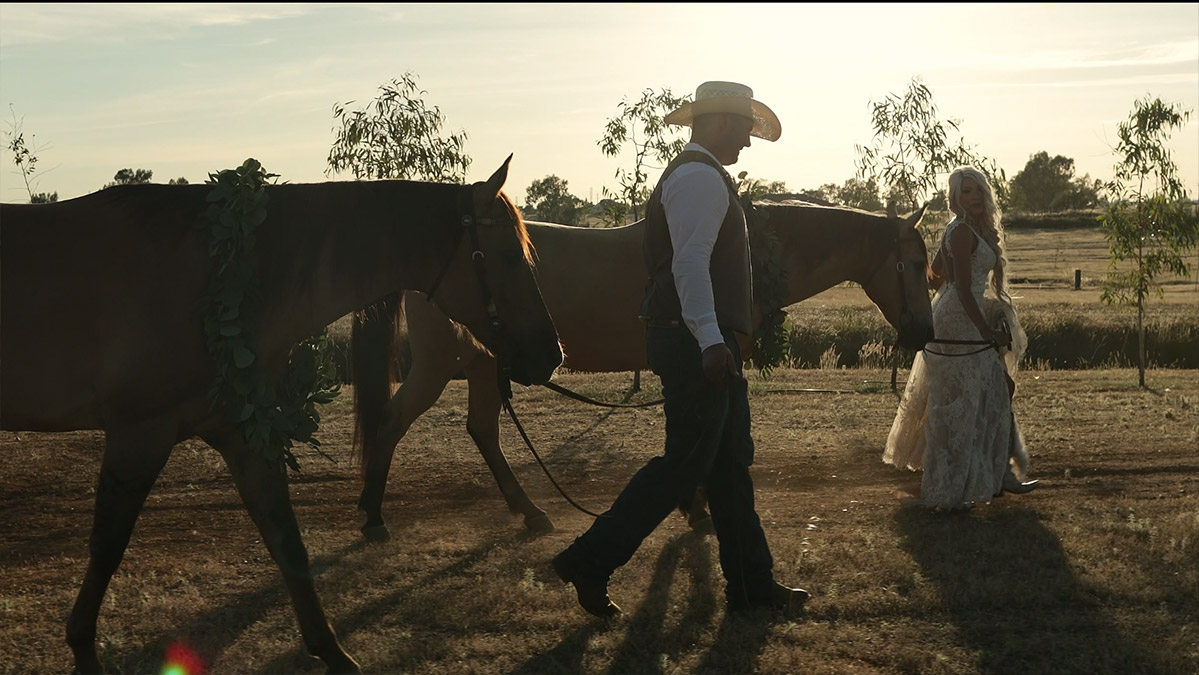 Bride and groom walking with their horses