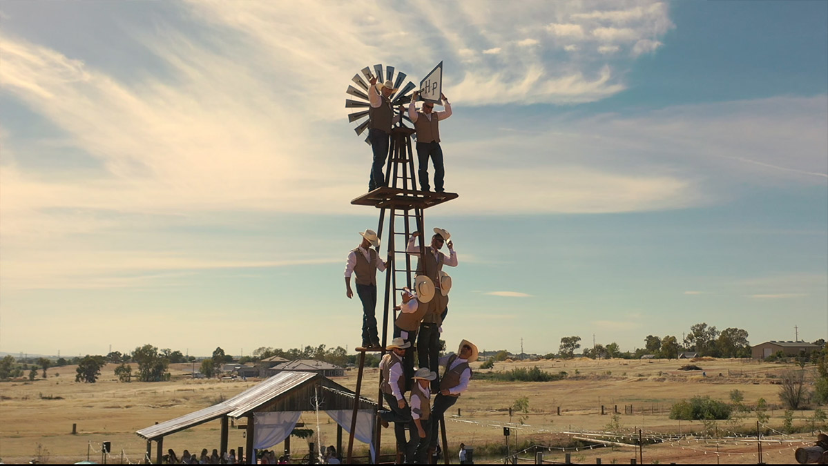 groom and his groomsmen climbing on a windmill