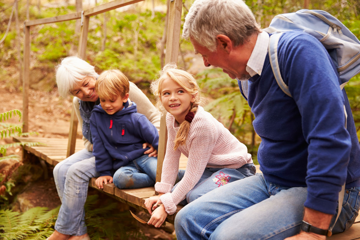 grandparents spending time with their young grandchildren by a stream in autumn