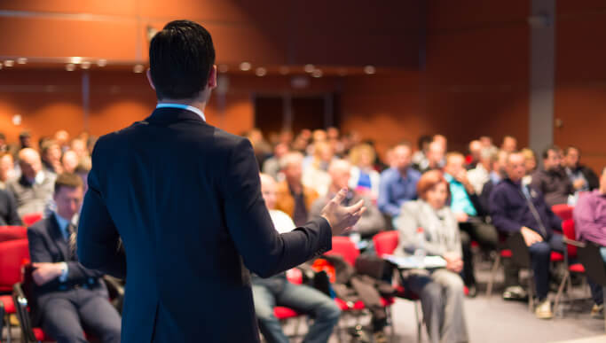 Business person speaking to audience in person