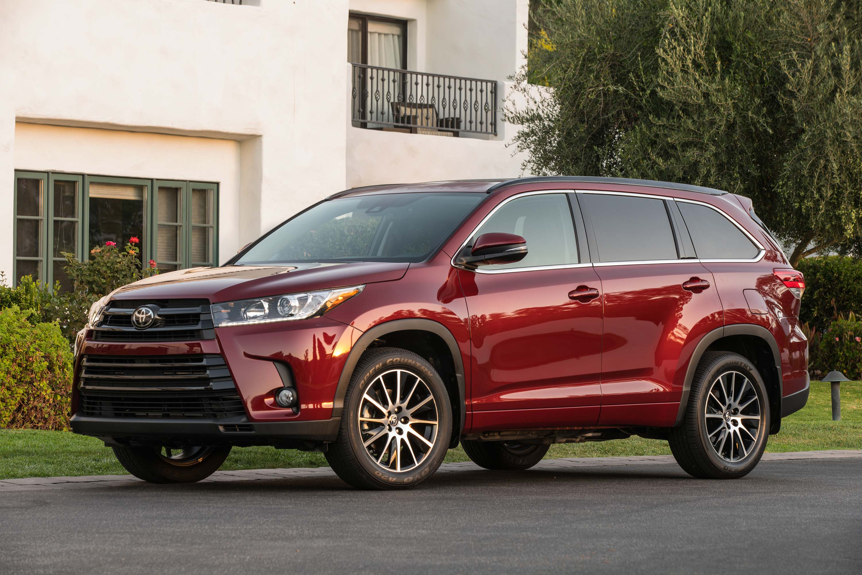 Red toyota highlander in front of a house