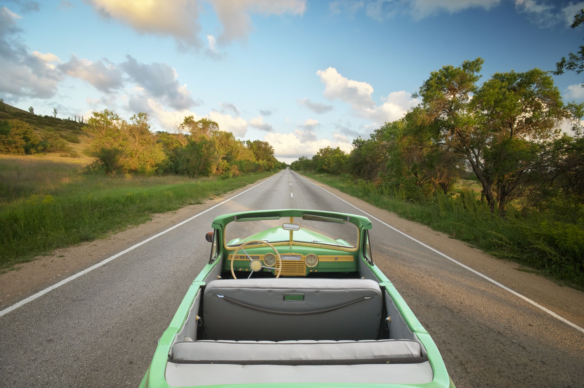 Green retro car on empty road