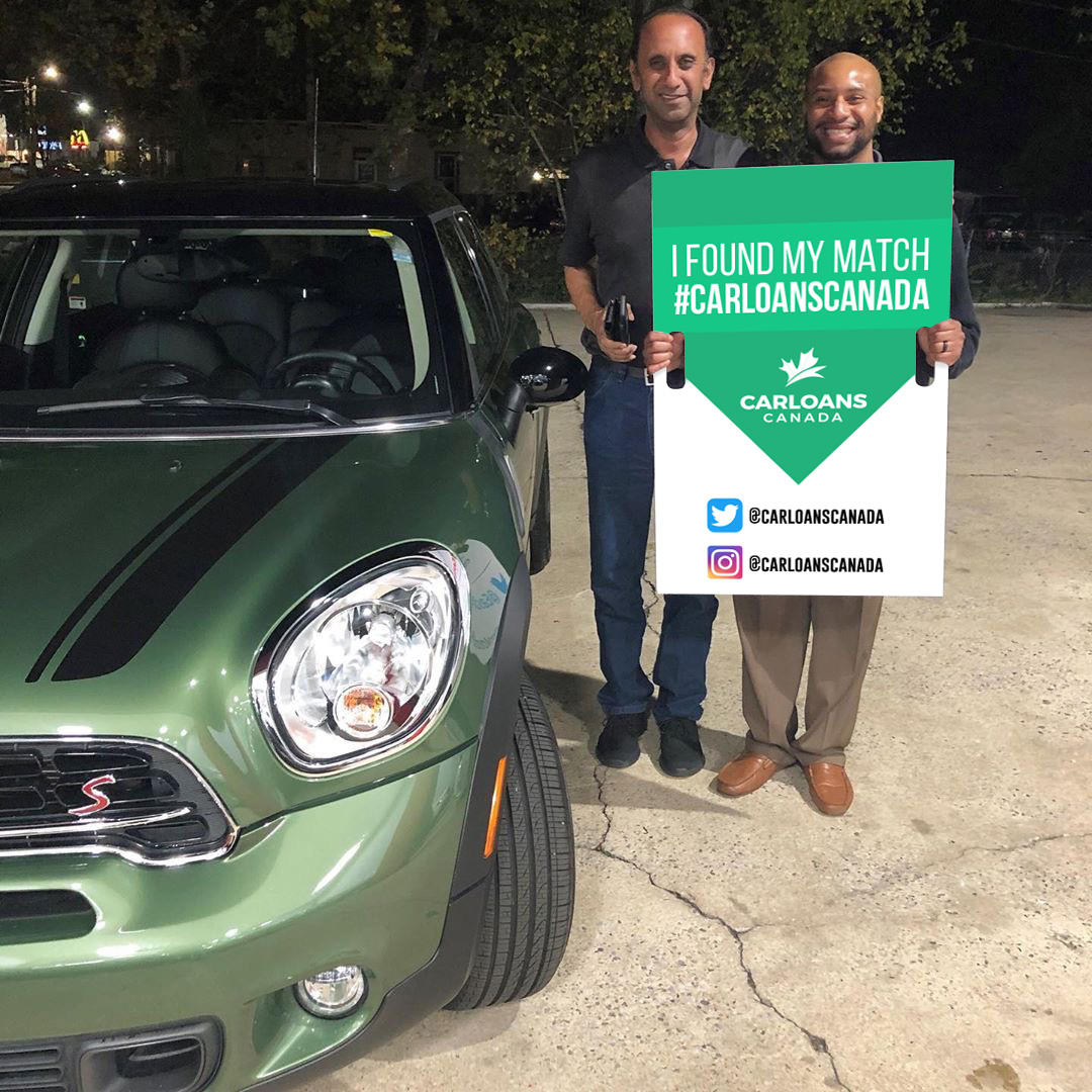Men in front of their electric mini cooper