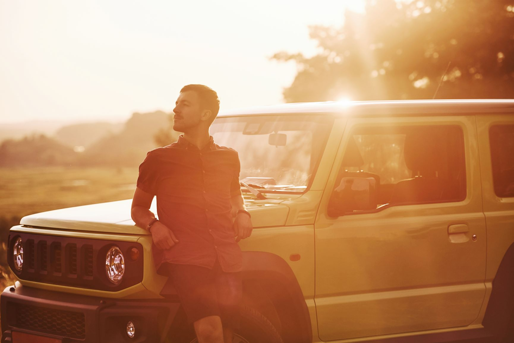 man at sunset in front of jeep