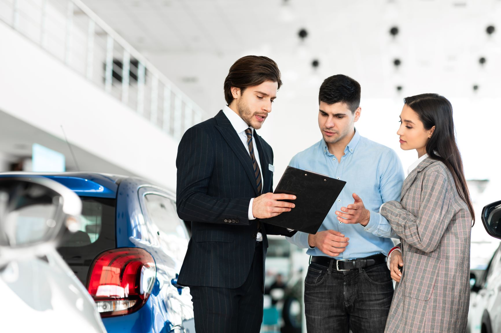 young couple with car salesman