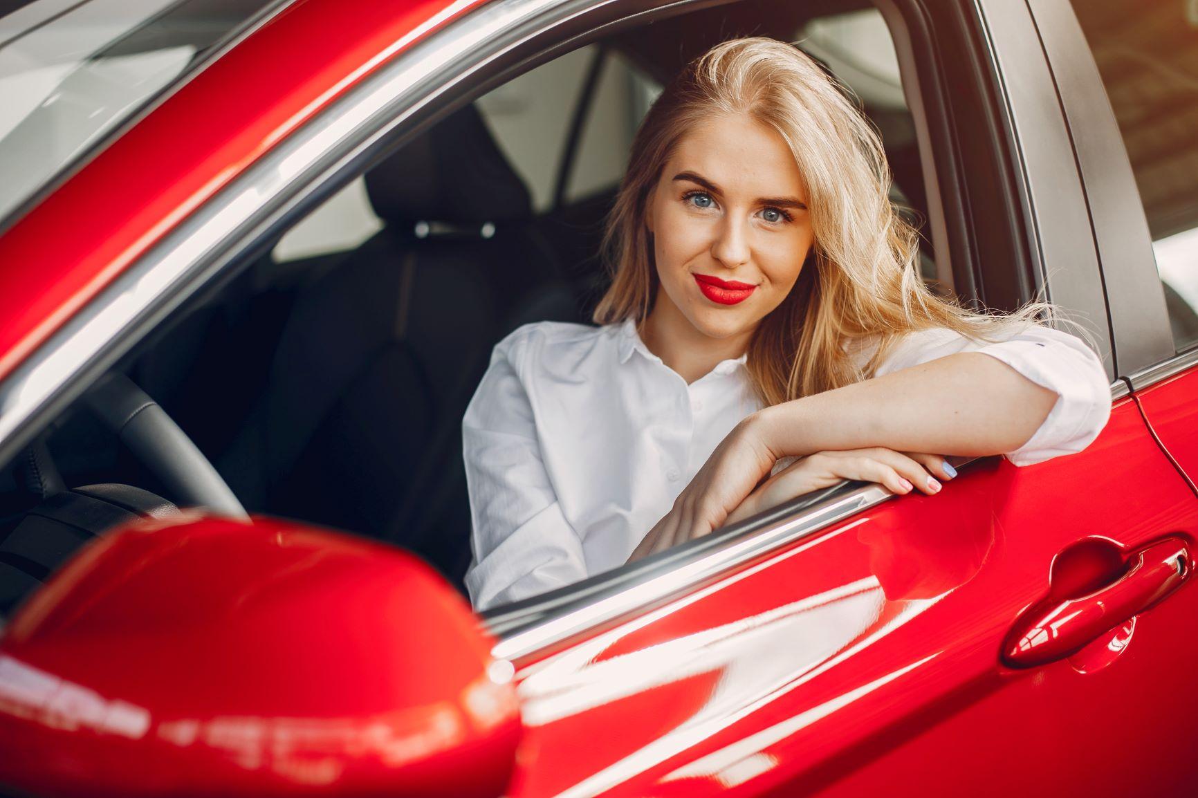Blonde hair girl in red car