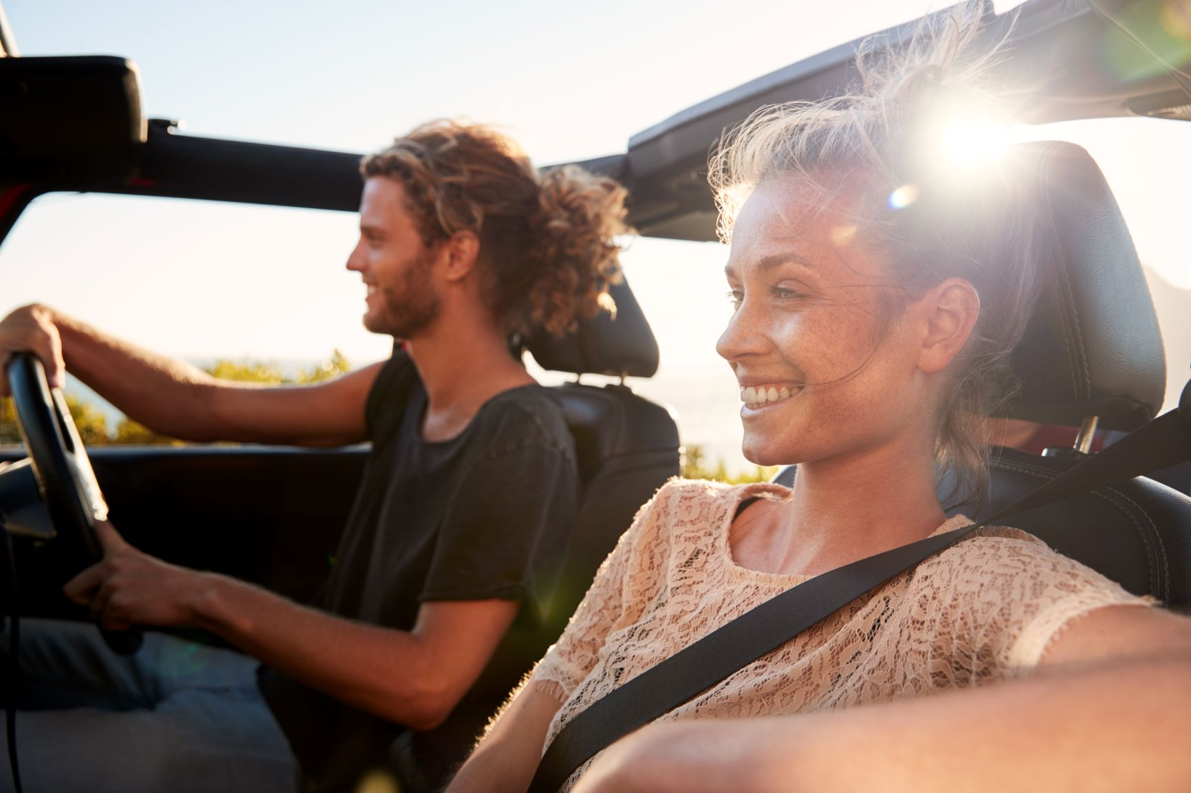 Couple driving car with top down