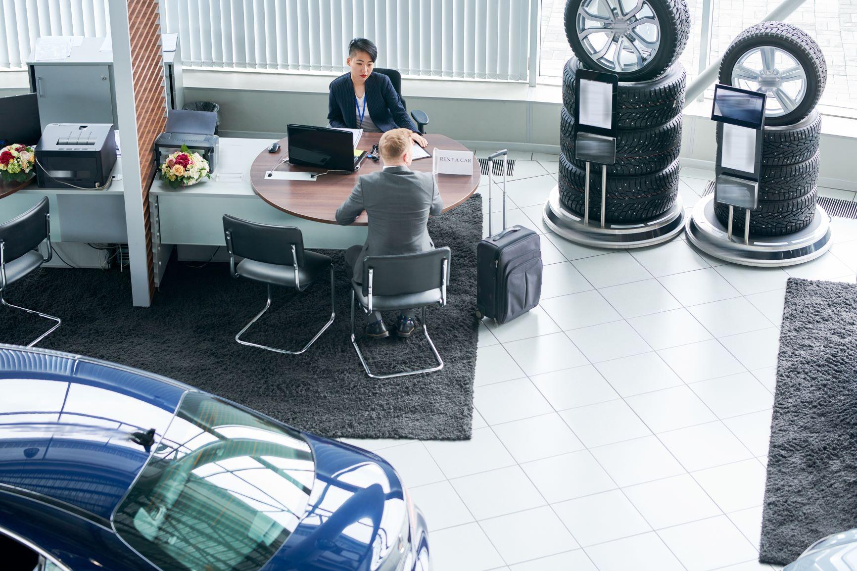 man at desk with female car salesperson at dealership
