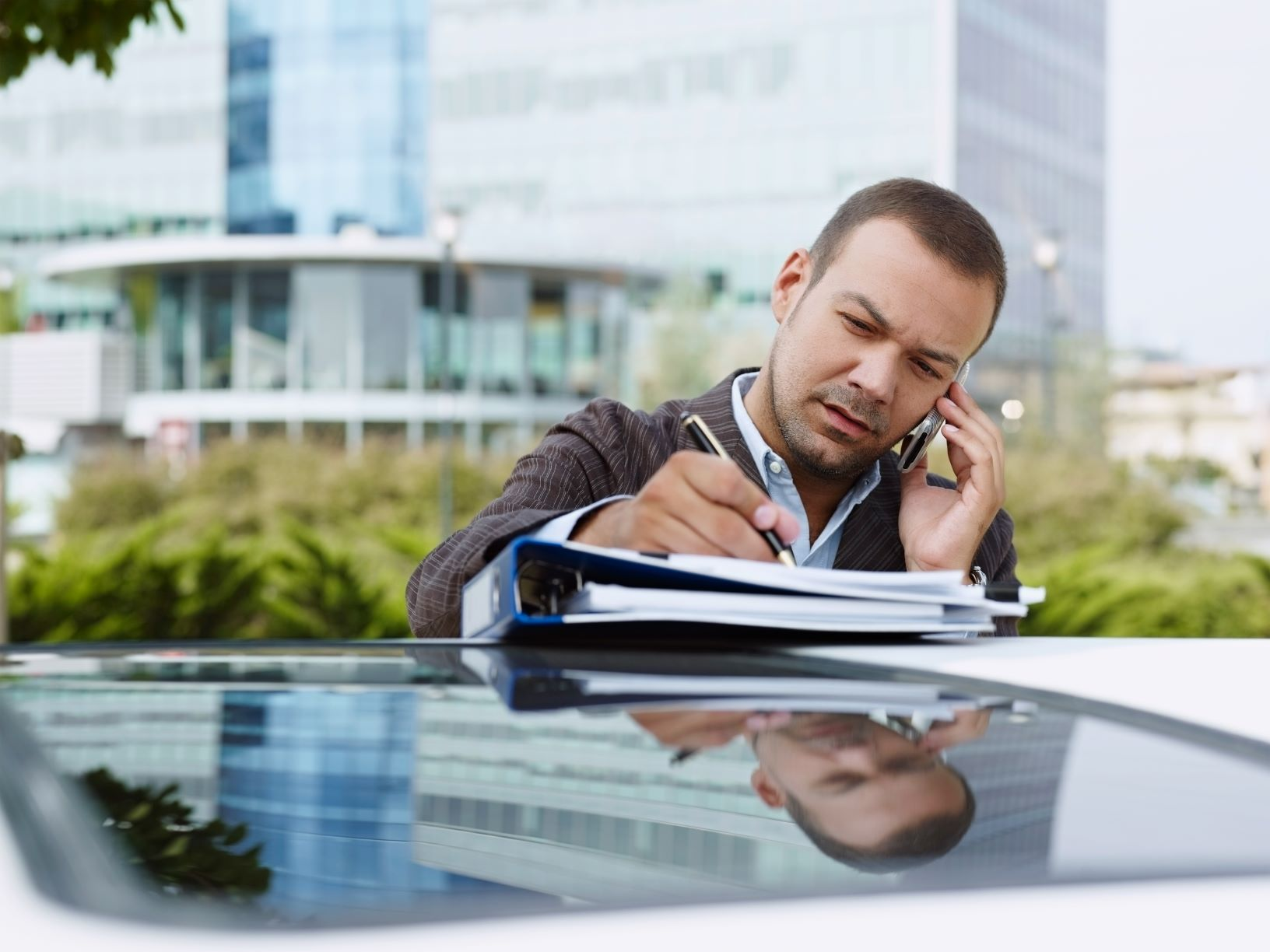 man doing paperwork outside on top of his car