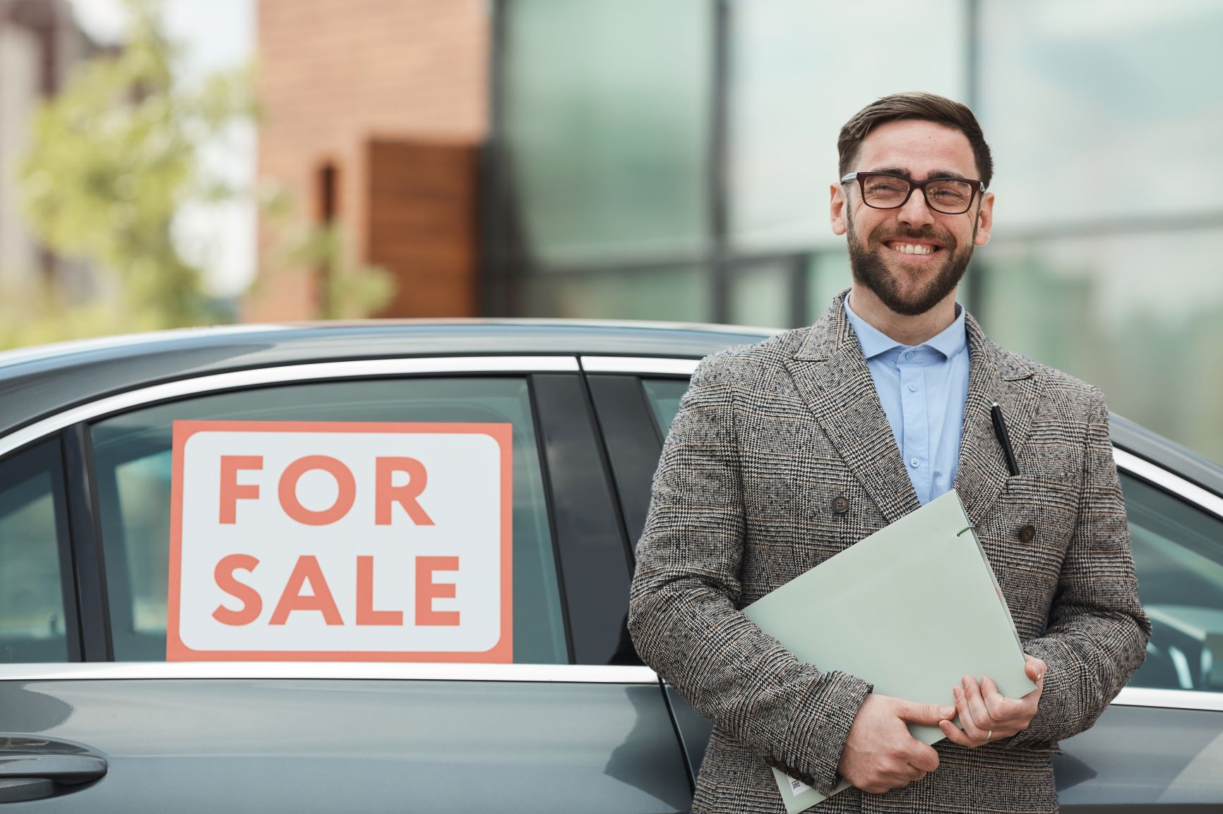 man standing in front of a car for sale