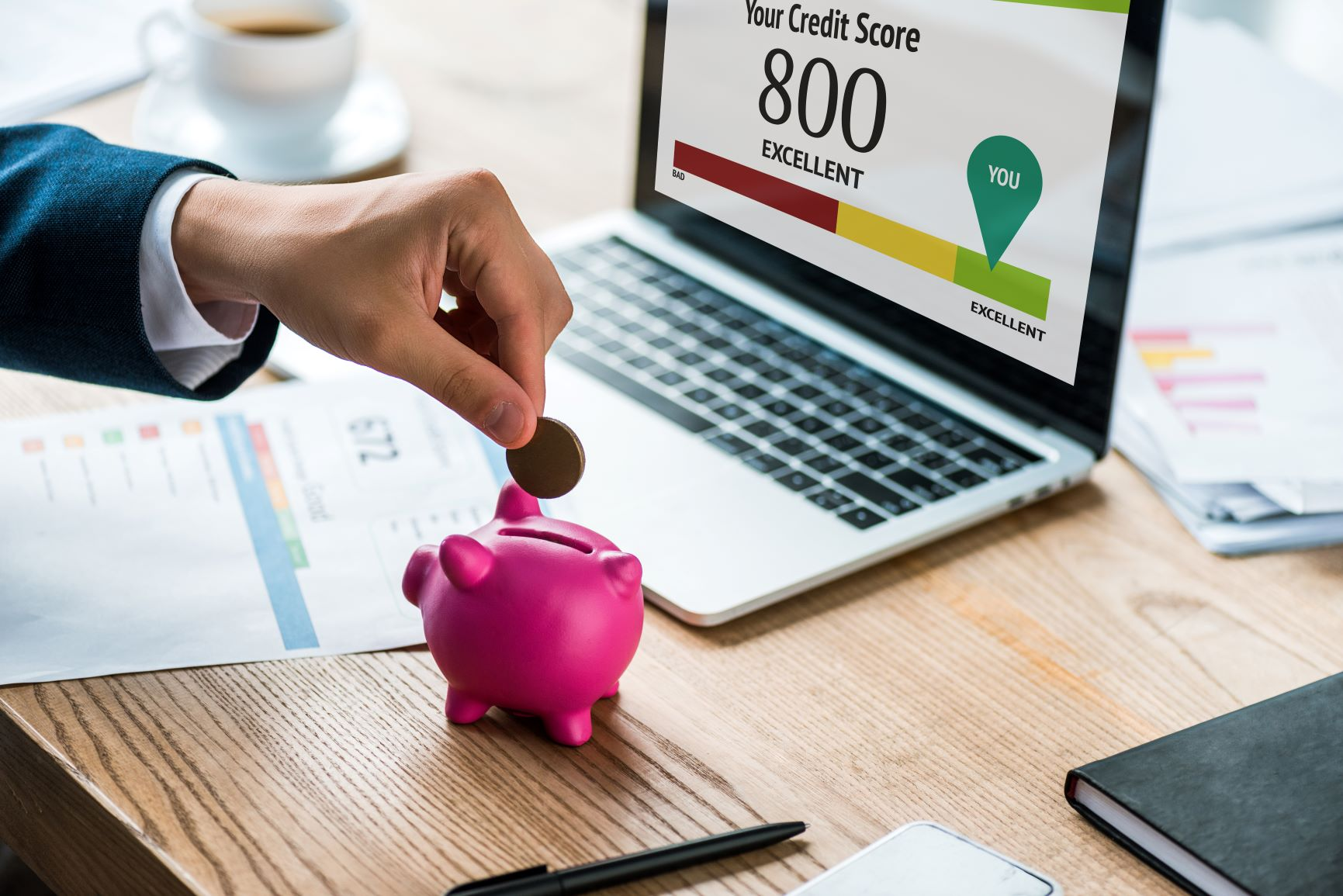 Piggy bank in front of credit score computer