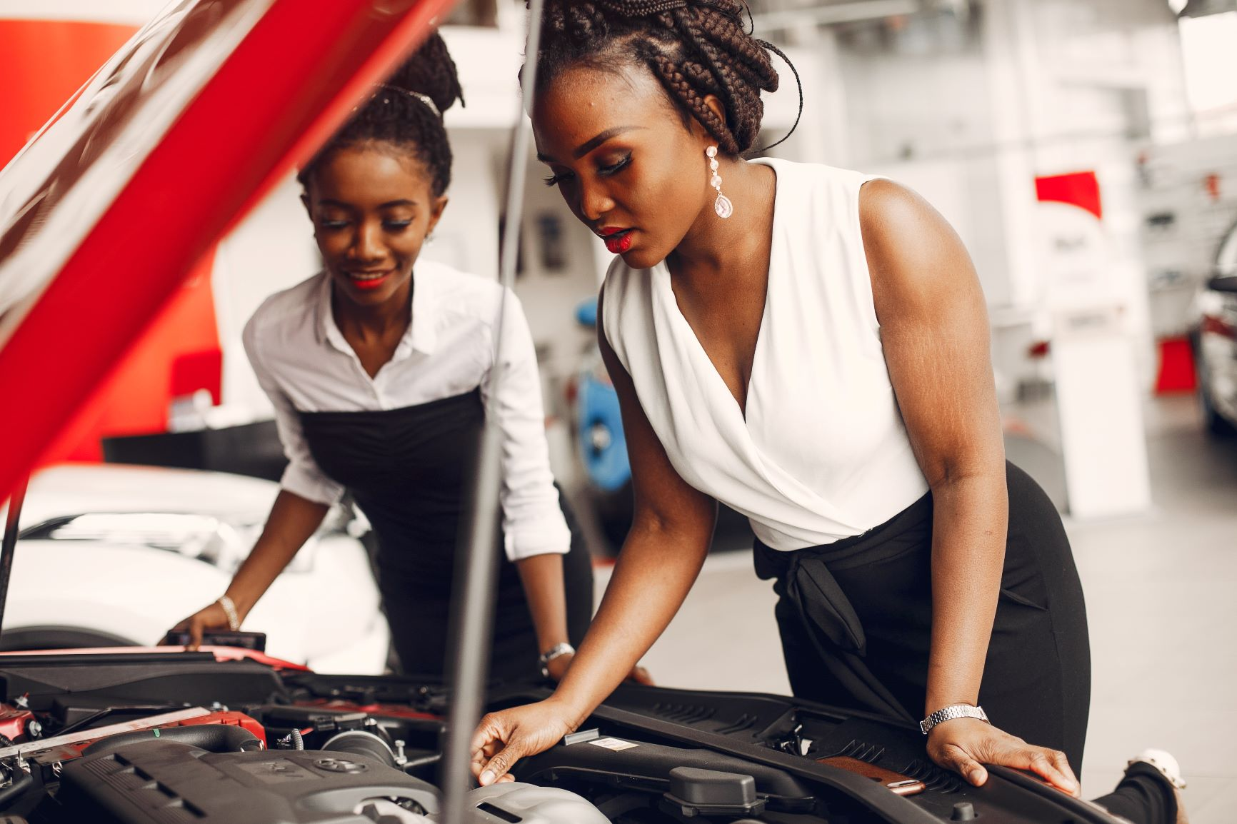 two women looking at a car engine